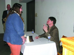 Bruce Mills explains to a YSU student the dynamics behind his memoir as he signs her book.