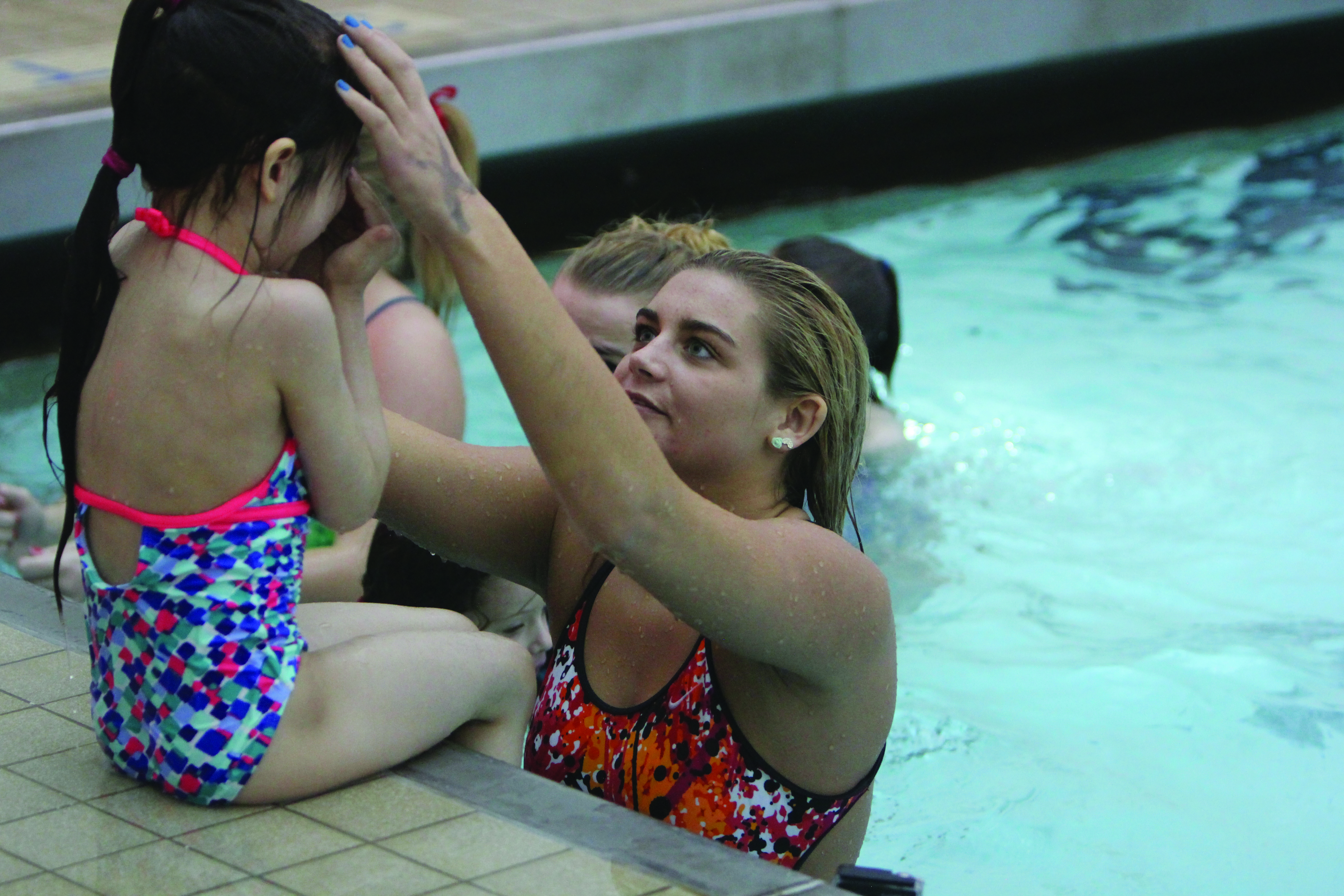 Members of the YSU swimming and diving team help children learn aquatics and swimming techniques as a fundraiser to offset traveling and equipment expenses.