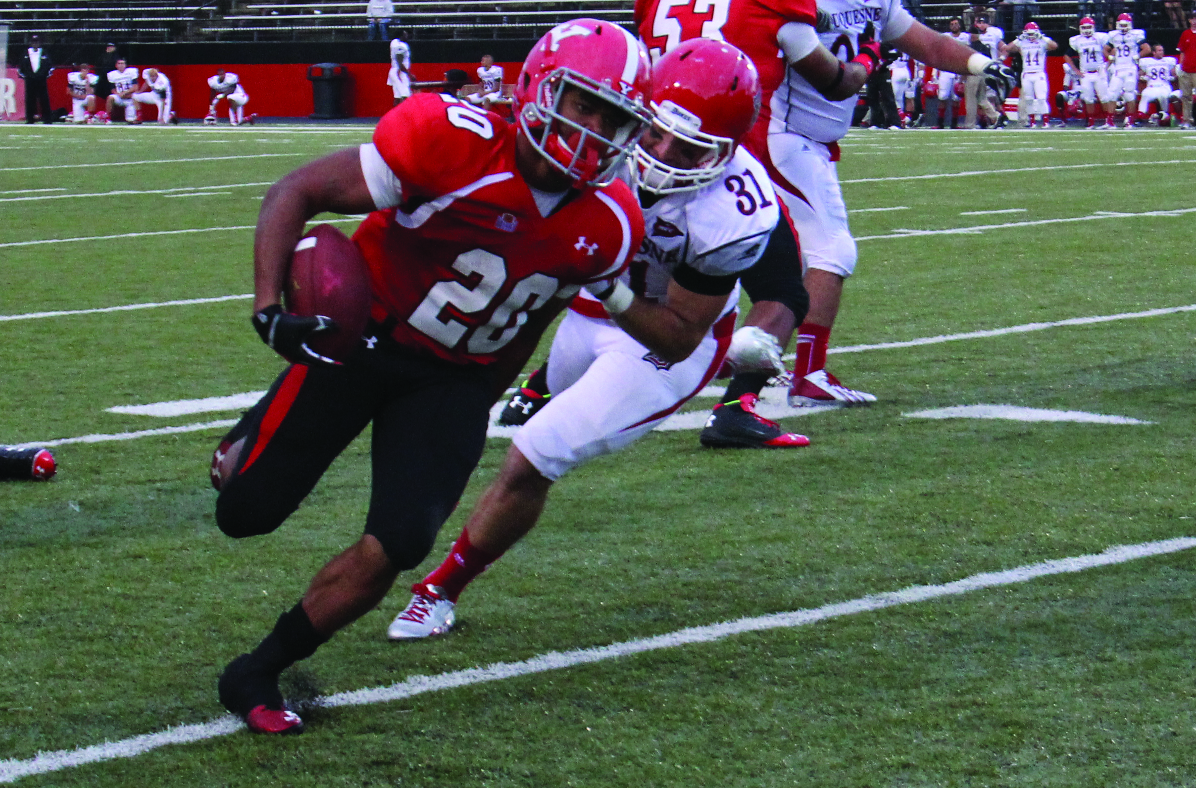 Youngstown State University's Jody Webb (20) evades a Duquesne University defender during a game in September of 2013. Photo by Dustin Livesay/ The Jambar.
