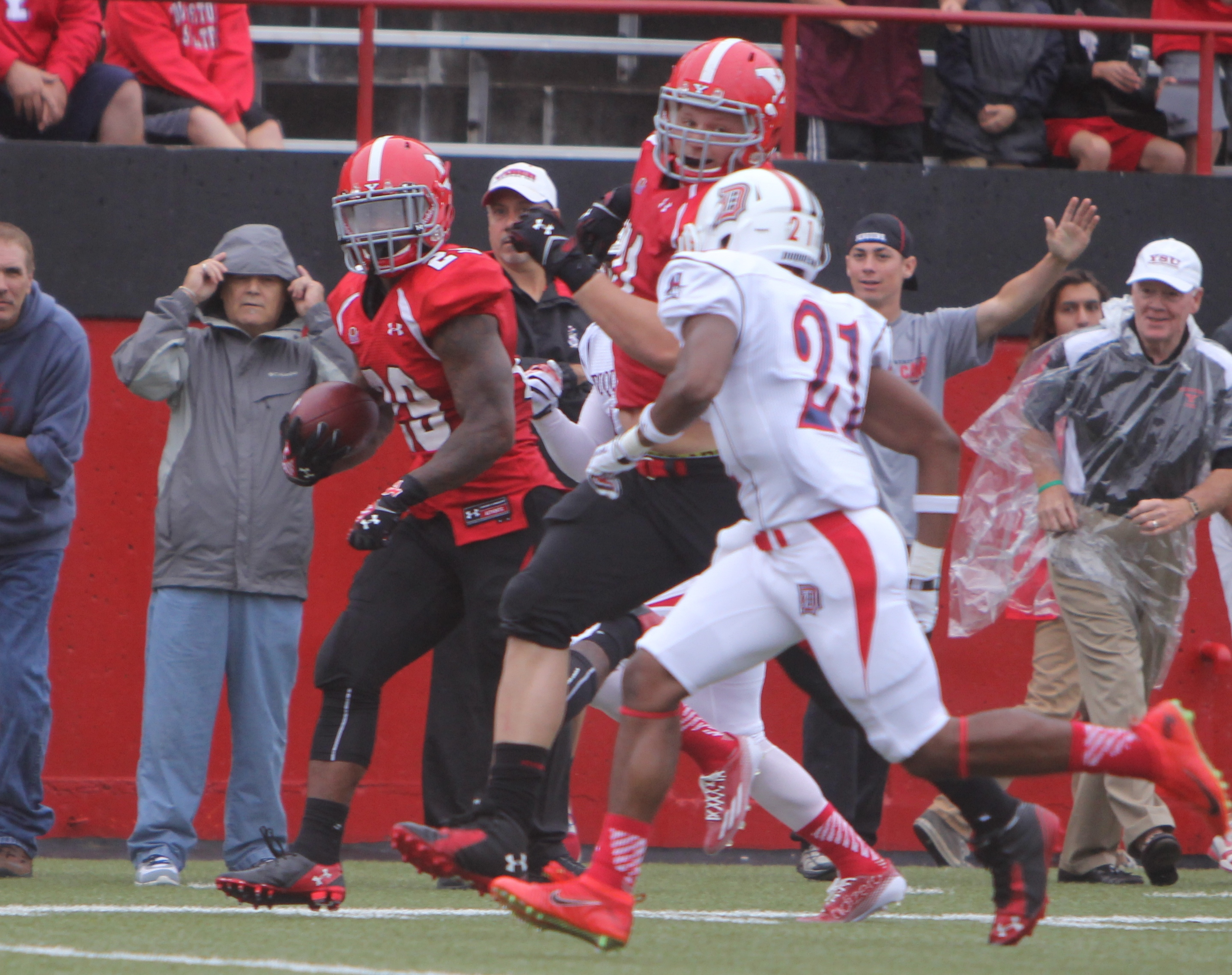 Youngstown State's Martin Ruiz (29) picks up a block from teammate Cameron Frazer (71) on Duquesne's Martin Brandon (21) during the first quarter of Saturday evenings matchup at Stambaugh Stadium.  Dustin Livesay  |  The Jambar
