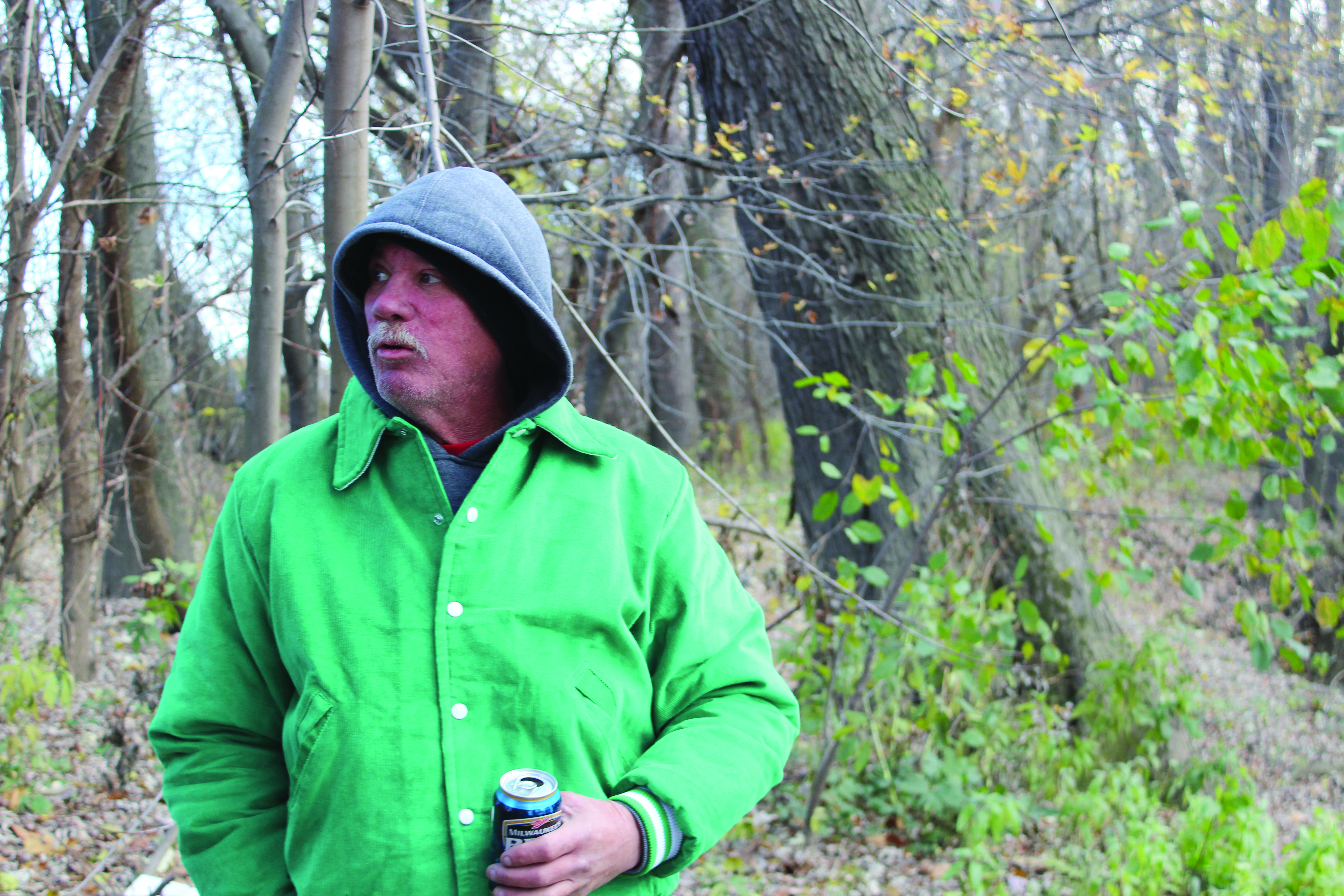 Tony Avery visits what remains of his home on the Mahoning River. The cabin burned to the ground three years ago and has been reclaimed by squatters. Photo by Billy Ludt/ The Jambar.