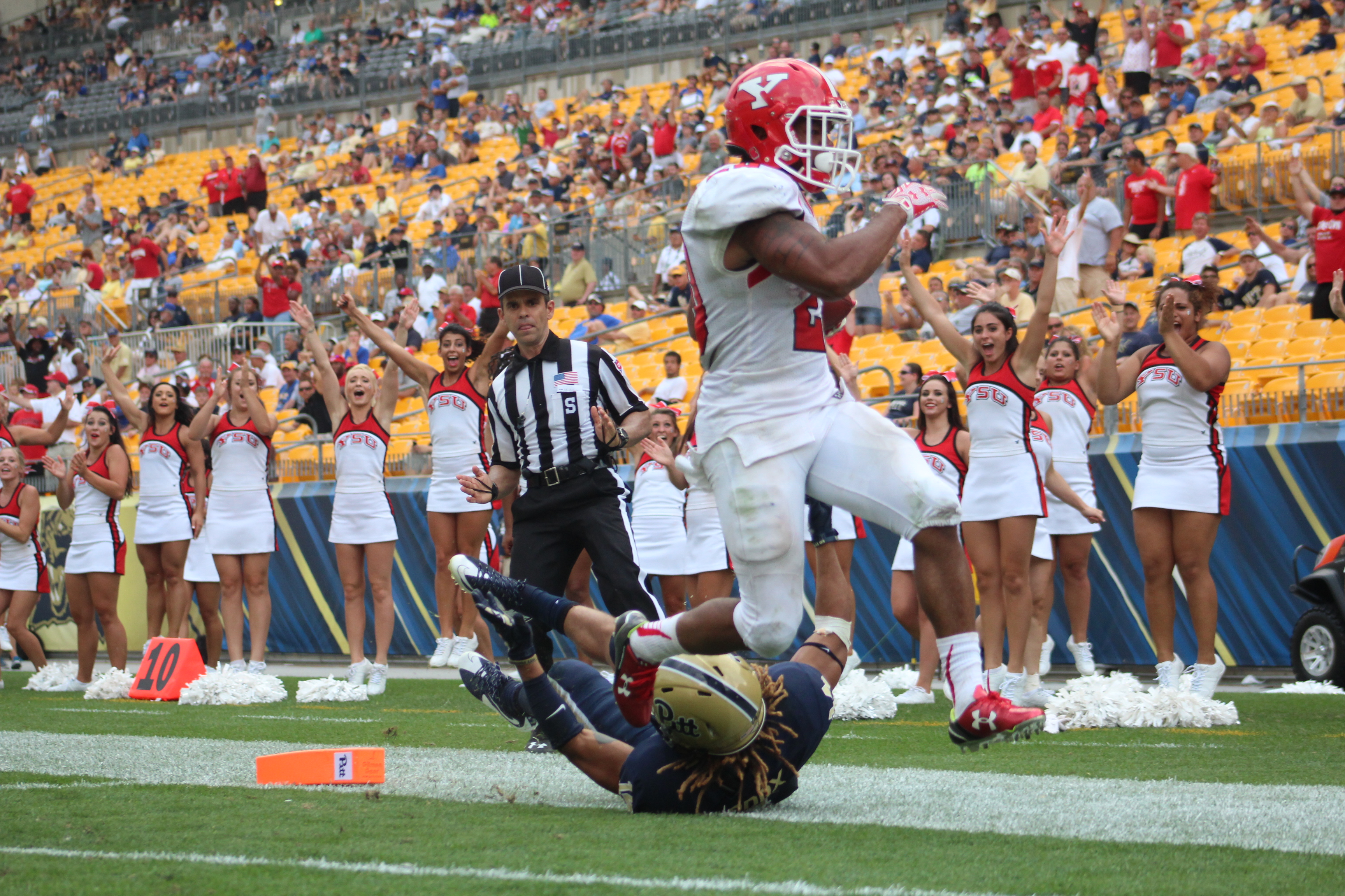 Youngstown State University running back Jody Webb (20) breaks a tackle from a Pitt defender as he scores his first touchdown of the season opener.
