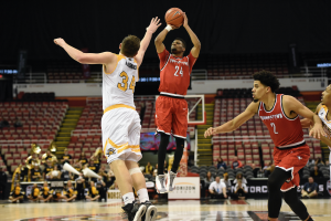 YSU guard Cameron Morse (24) pulls up for a jumper over NKU forward Drew McDonald (34).