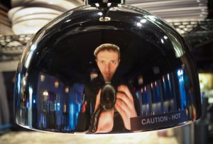 Bradley Miller takes a self-portrait in a metal food cover. Miller was named the head chef at Suzie's Dogs and Drafts, a restaurant opening downtown. Photo courtesy of Bradley Miller.