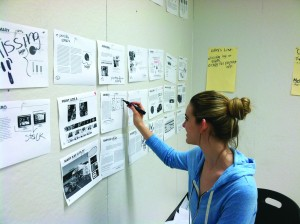 Christy hartman works on the layout of the team's plan book.