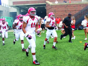 Derek Rivers (11) runs with his teammates onto the field for the season opener against Illinois at the University of Illinois on Aug. 30.