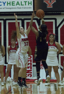 Youngstown State University guard Jenna Hirsch (32) attempts to block a shot from an Oakland University player.