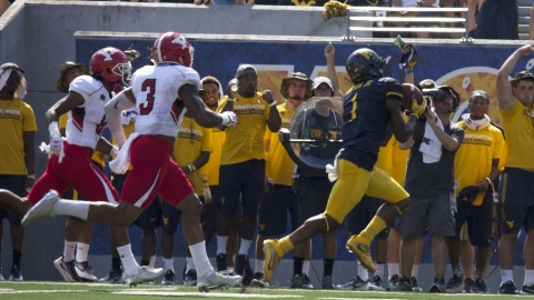 West Virginia University receiver Shelton Gibson (1) makes an over-the-shoulder catch against two Youngstown State University defensive backs.