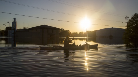 Buckley Miller paddles a canoe past a flooded water treatment plant in downtown Lumberton, N.C., after Hurricane Matthew caused downed trees, power outages and massive flooding along the Lumber River, on Tuesday, Oct. 11, 2016. (Travis Long/Raleigh News & Observer/TNS)